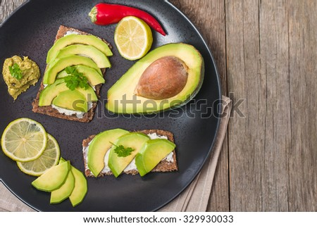 Avocado sandwich with ingredients in plate on wooden background - stock photo