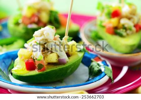 avocado stuffed with crabmeat, mango, red onions - stock photo
