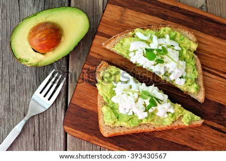 Avocado toast with egg whites and pea shoots on wooden board, overhead view - stock photo