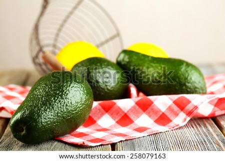 Avocado with lemons on napkin on wooden table close up - stock photo