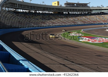 AVONDALE, AZ - NOV. 14: Fans watch a practice session for the NASCAR Sprint Cup Checker O'Reilly Auto Parts 500 race, at Phoenix International Raceway on Nov. 14, 2009 in Avondale, AZ. - stock photo
