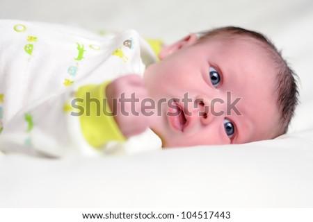 Awake Infant with Blue Eyes. Three-week old baby boy laying on white blanket. Shallow DOF. - stock photo