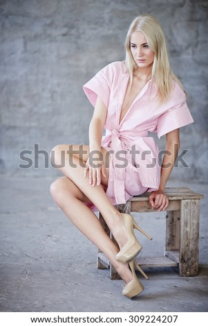 Awesome blond woman in pink dress sitting on wooden chair over light grey background. - stock photo