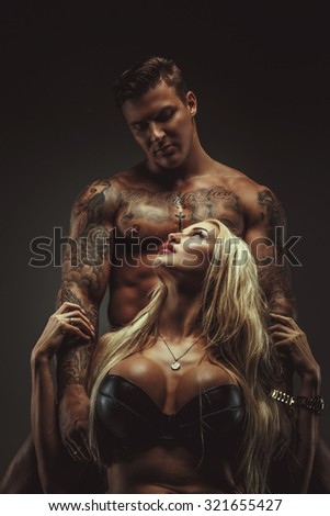 Awesome blond woman in underwear and shirtless muscular man with tattoes isolated on grey bachground. - stock photo