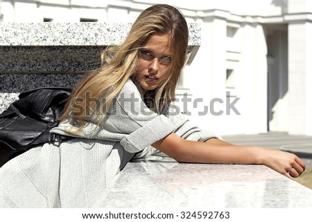 Awesome blonde woman with black backpack in grey clothes posing outside on white building background - stock photo