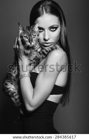 Awesome caucasian attractive sexy fashion model with long brunette natural hair, beautiful eyes, full lips, perfect skin posing  in studio, holding Bengalian cat, beauty photo shoot, retouched image - stock photo