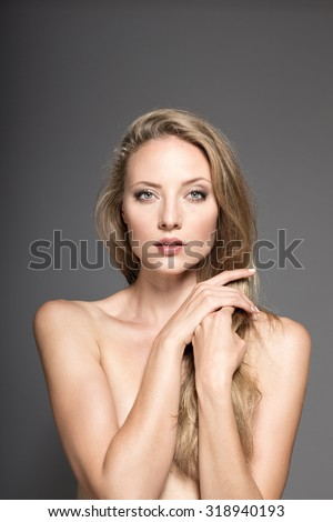 Awesome caucasian attractive sexy professional fashion model with blond hair posing in studio topless, perfect make up, tanned skin, isolated on gray background, retouched image - stock photo