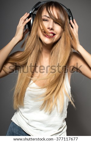 Awesome caucasian attractive sexy professional female model with long hair posing in studio wearing white shirt and wireless headphones, isolated on grey background - stock photo