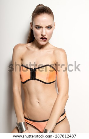 Awesome caucasian attractive sexy sports model, long brunette natural hair, beautiful eyes, perfect skin posing in studio in orange swimwear and metal bracelets, beauty photo shoot, retouched image - stock photo