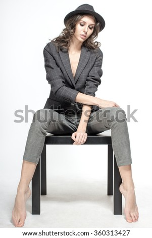 Awesome Caucasian attractive shy sexy female model with brunette hair posing on table in studio, wearing formal suit and hat, isolated on white background - stock photo