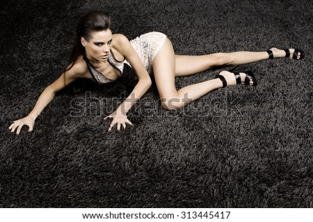Awesome caucasian sexy fashion model with stylish hairstyle, long legs, full lips, perfect skin, wearing transparent cocktail dress, laying on shiny black carpet, beauty photoshoot, retouched image - stock photo
