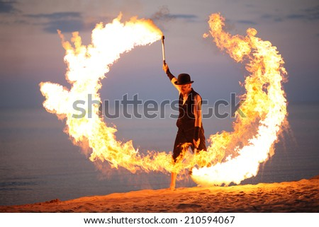 Awesome fire show on the beach; circle of flame - stock photo