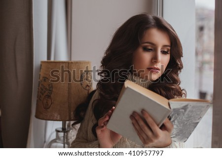 Awesome girl resting at home reading a book. A woman sits on the windowsill and presses the book to himself, dreamily looking out the window, space. - stock photo