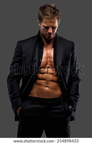 Awesome male in black suit dressed on naked torso. Isolated on grey - stock photo
