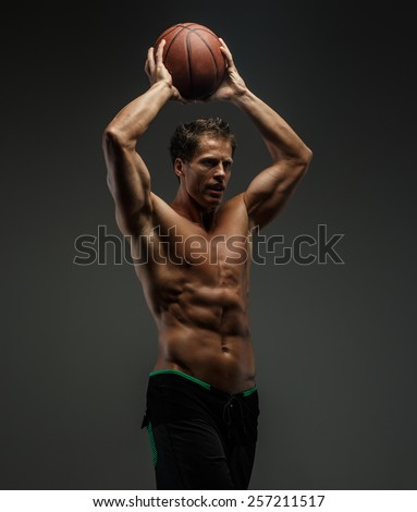 Awesome muscular male in black shorts with basket ball in a hands. Grey background. - stock photo