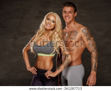 Awesome positive couple of sexy blond fitness woman and strong muscular tattooed man. - stock photo