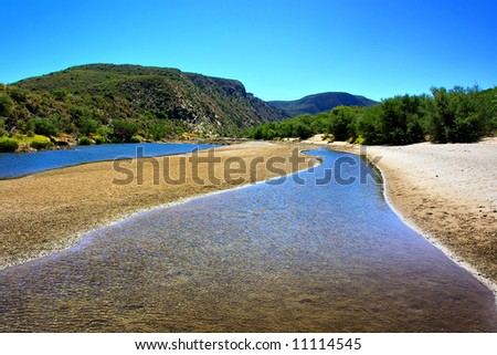 Awesome river in mountains looking like a road. Shot in the Langeberge highlands near Grootrivier and Gouritsrivier rivers crossing, Garden Route, Western Cape, South Africa. - stock photo