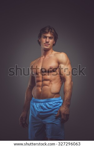 Awesome shirtless bodybuilder in blue shorts posing over grey background. - stock photo