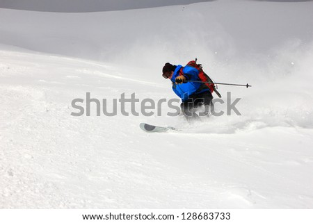 Awesome skier with a plume of fresh powder snow. - stock photo
