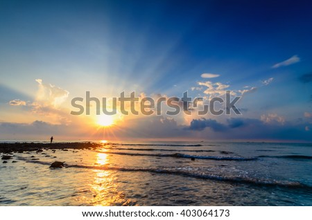 Awesome sunrise with marvelous clouds at Black Stone Beach, Kuantan, Malaysia.Flare & Ray of light is visible. Men fishing at the end of the beach. - stock photo