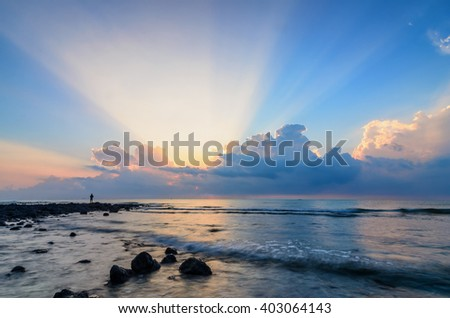 Awesome sunrise with marvelous clouds at Black Stone Beach, Kuantan, Malaysia. Ray of light is visible with reflective black stones on the foreground. - stock photo
