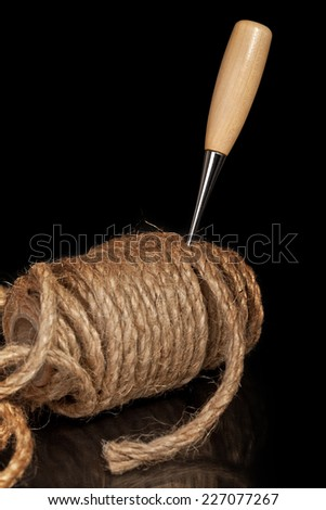 Awl stuck in the coil jute rope on a black background - stock photo