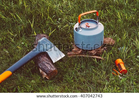 Axe, campfire kettle and matches. You can make tea or coffee on fire. Outdoor food items set. Travel, tourism and camping equipment. Picnic rest, cooking on the nature. Summer BBQ and grill tools. - stock photo