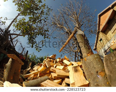 Axe in Chopping Block and Firewood.Axe and pile of chopped firewood - stock photo