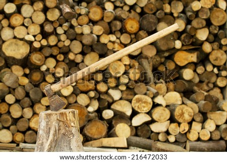 Axe near firewood stack  - stock photo