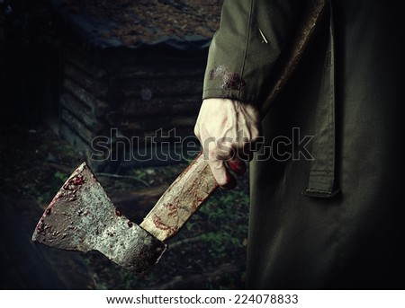 Axe with blood in male hand.  murderer or butcher, halloween theme - stock photo