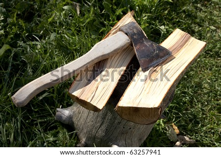 Axe with  pack for cabin against a green grass - stock photo