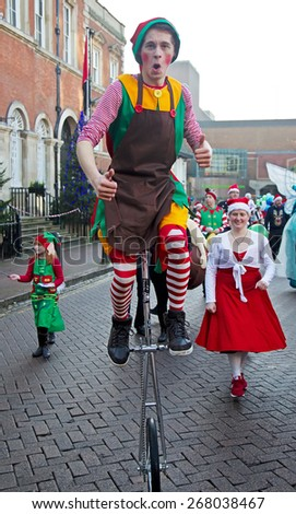 AYLESBURY, UK - NOVEMBER 30: A unicyclist performer parades through the market square in Aylesbury along with other carnival acts as part of the Christmas festivities on November 30, 2014 in Aylesbury - stock photo
