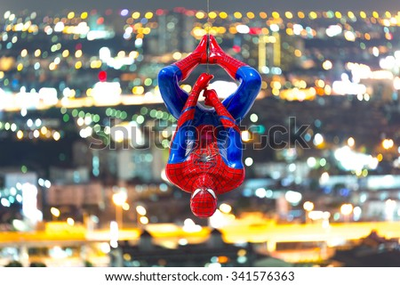 Ayuttaya, Thailand - November 15, 2015 : Spider-Man model upside down on cityscape background. - stock photo