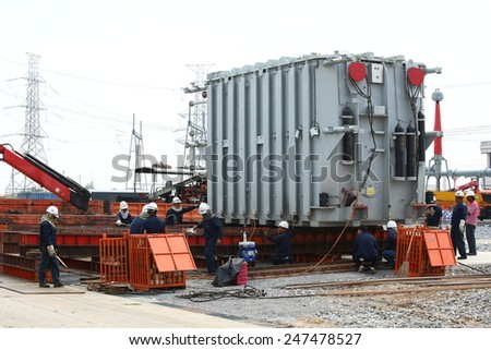 AYUTTHAYA -THAILAND - JANUARY 10 : The construction of electrical substation with workers transported a large old transformer, January 10, 2014 in Ayutthaya province, Thailand - stock photo