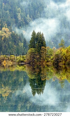 Azure lake in the mist. Jiuzhaigou Valley was recognize by UNESCO as a World Heritage Site and a World Biosphere Reserve - China - stock photo