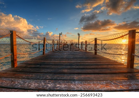 Azure waters behind a wooden pier with railings - stock photo