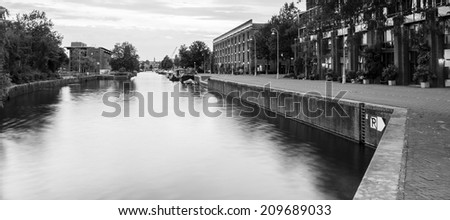 B+W Entrepotdok canal, Amsterdam 4. A shutter speed of 8 seconds was needed to blur the reflection on the water. - stock photo