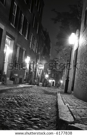 b/w image of an old 19th Century cobble stone road in Boston Massachusetts, lit only by the gas lamps revealing the shuttered windows and brightly lit doorways of the rowhouses on Acorn Street - stock photo