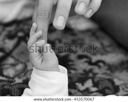 B&W photo of new-born baby hand in mother's palm - stock photo
