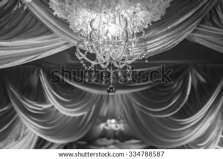 B&W wedding ceremony arches decorated with fabrics, chandeliers and bouquet. - stock photo