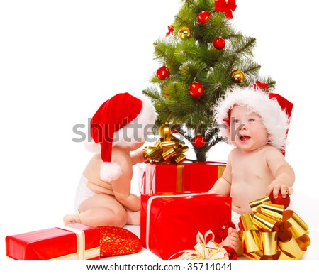 Babies looking for their presents under Chistmas tree - stock photo