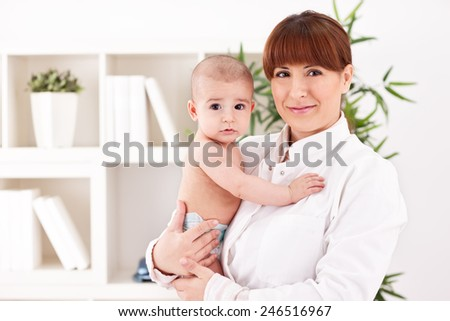 Baby and doctor pediatrician in office - stock photo