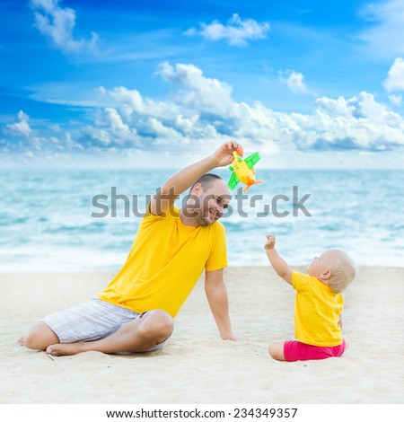 Baby and father on the tropical beach playing toy plane - stock photo