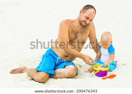 Baby and father on the tropical beach playing toys - stock photo