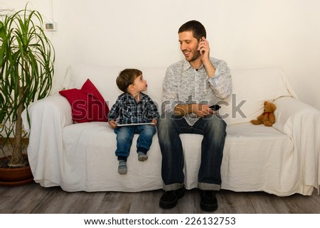 Baby and father playing with tablet and smiling themselves on a white sofa while father is making a phone call with red pillow and little bear - stock photo