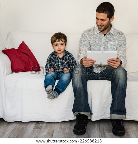 Baby and father playing with tablet on a white sofa while baby i - stock photo