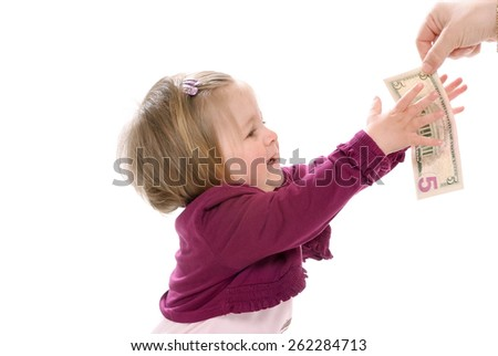 Baby and five dollars Mother gives the baby a banknote five U.S. dollars  - stock photo