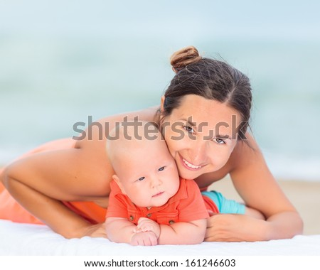 Baby and mom are relaxing on sunbed - stock photo