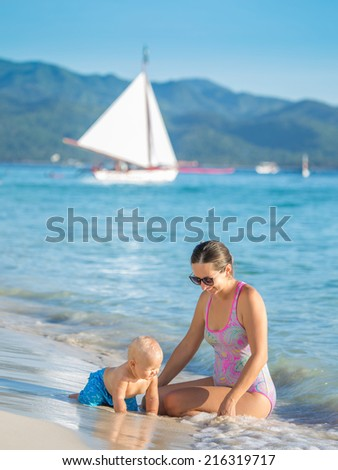 Baby and mother on the tropical beach - stock photo