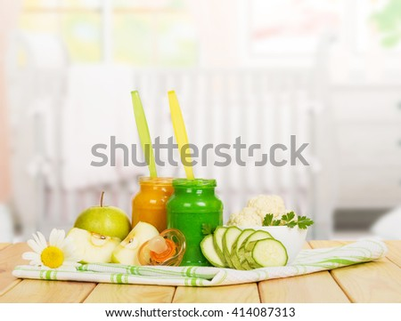 Baby apple puree, vegetable, dummy and cloth on a background of the kitchen. - stock photo